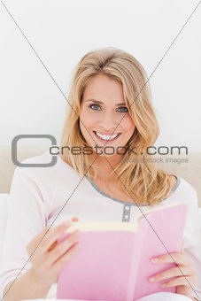Close up, Woman smiling with book in hand, sitting in bed