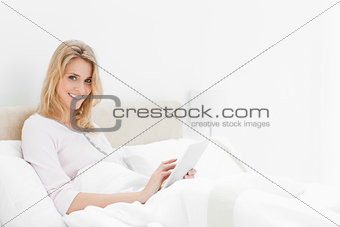 Woman sitting in bed, with tablet pc in hand, looking up and smi