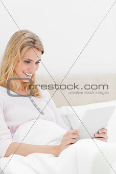Woman sitting in bed, holding a tablet with both hands, and smil