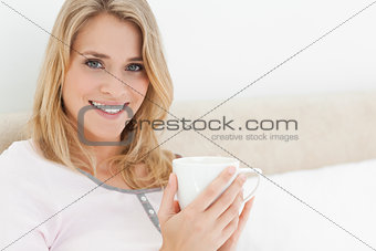 Close up, Woman holding a cup in her hands, while looking ahead