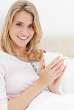 Close up, Woman in bed, with cup in hands as she looks forward s