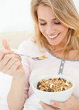 Close up, woman with a bowl and raised spoon of cereal in her ha
