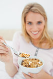 Focus shot, woman offering a spoon of cereal, focused on the spo