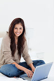 Woman smiling as she looks sideways, with her laptop on the bed