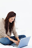 Woman smiling as she uses her laptop on her bed