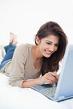 Close up, woman lying on the bed smiling with her laptop in fron