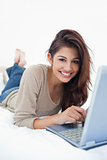 Woman smiling in front of her laptop, lying on the bed with her