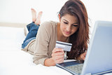 Woman looking at her credit card details as she uses her laptop