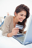 Close up , woman with credit card looking at laptop and smiling