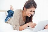 Woman smiling as she scrolls through her tablet on the bed