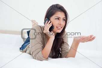 Woman making a phonecall glancing to the side as she lies on the