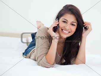 Woman smiling and looking in front of her as she makes a phoneca