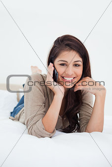 Close up, woman making a phonecall on the bed and smiling as she