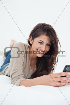 A woman smiling as she looks in front of her with her phone in h