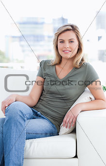 Close up, woman sitting on the couch with crossed legs and a smi