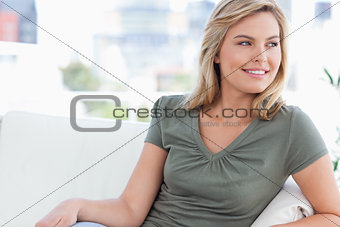 Close up, woman smiling and sitting on the couch looking to the