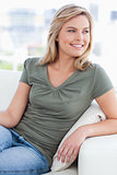 Woman looking to her side while smiling and sitting on the couch