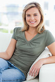 Woman looking ahead, smiling and resting her arm on the couch ar