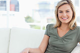 Woman sitting on couch and smiling, while looking forward