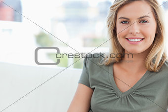 Close up, woman smiling as she sits on a couch