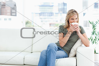 Woman holding a mug up to her nose as she looks to the side whil