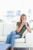 Woman with her legs crossed, holding a mug to her nose and looki