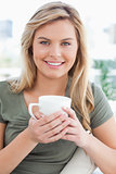 Close up, woman smiling, with mug in her hands and looking ahead