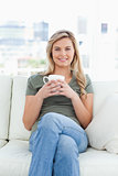 Centered shot, woman sitting on the couch with a cup in hands an