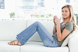 Woman sitting sideways on the couch, looking forward and cup rai