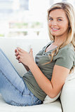 Close up, woman sitting across couch, cup in hands looking forwa