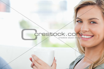 Woman smiling, looking forward and holding up a mug in hands