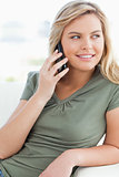 Close up, woman making a call while looking to the side and smil