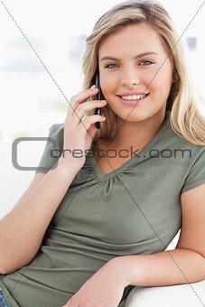 Close up, woman making a call, smiling and looking straight ahea