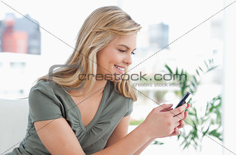 Woman smiles as she uses her phone while on the couch