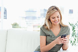 Woman sits on the couch, looking and using her phone and smiling