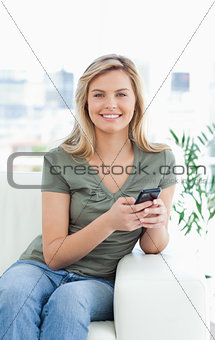Close up, woman smiling as she uses her phone, while looking for
