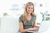 Woman smiling and looking forward as she uses a laptop on the co