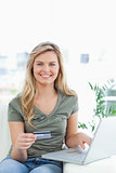 Woman using her credit card and laptop on the couch while smilin