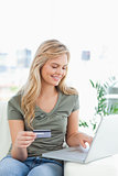 Woman smiles as she looks at her laptop with credit card in hand