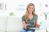 Woman looking ahead and smiles as she holds her credit card, and