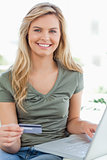 Close up, woman using her credit card and laptop while smiling a