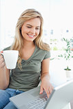 Woman smiling as she uses her laptop and holds a cup in her free