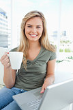 Woman looking forward with a cup in her hand, as she uses her la