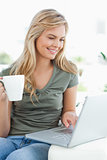 Woman smiling, as she uses her laptop and hold a cup in her othe
