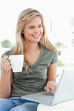 Woman looking slightly to the side, as she holds a cup in her ha