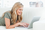 Woman smiling as she uses her laptop while lying across the couc