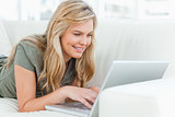 Woman lying across the couch using her laptop and smiling