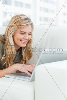 Close up, woman on the couch, using her laptop and smiling