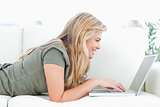Woman using her laptop and smiling as she lies on the couch