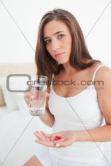 Woman with pills in one hand and a glass of water in the other l